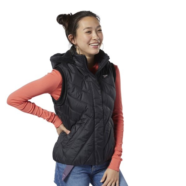 Show off sporty style while staying warm. This women\'s slim-fitting vest features a chevron-quilted pattern for a feminine, modern touch. A high collar helps keep your neck warm. The detachable hood and pockets are lined with Sherpa fleece for a cozy feel. Shell and lining: 100% polyester woven; Filling: 100% polyester padding Slim fit High neck for added coverage Sherpa fleece-lined detachable hood and pockets Full zip with flap closure Imported