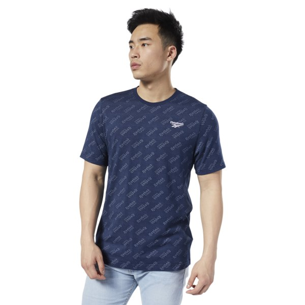 An everyday essential dressed up. A textured jacquard fabric with an allover monogram print adds some class to this men\'s t-shirt. The print is subtle and tonal for an understated look. A droptail hem in the back provides extra coverage. 100% cotton single jersey Regular fit Allover Reebok print Droptail hem for added coverage We partner with the Better Cotton Initiative to improve cotton farming globally Imported