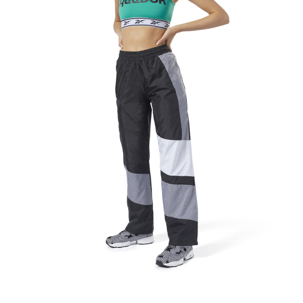 Made for speed. Retro \'90s and 2000s motocross style inspires these women\'s track pants. They\'re made of plain weave fabric for a crisp, smooth feel. Geometric panels and a graphlite print give them a throwback vibe. 100% polyester plain weave Regular fit Drawcord on elastic waist for adjustability Side slip-in pockets Reebok Vector logo on hip Imported