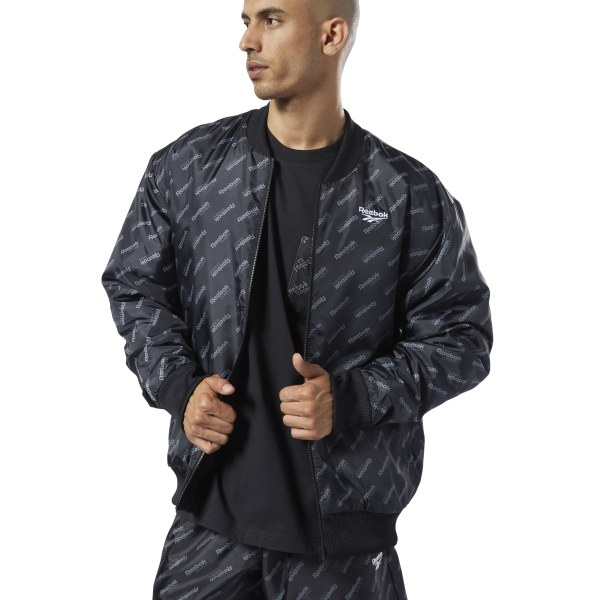 Straightforward, versatile style. This men\'s bomber jacket is fully reversible so you can wear it two ways. One side has a repeating monogram print, while the other keeps it simple with a neutral color and small logo. The lightly padded jacket is made of all-recycled polyester plain weave for a slightly shiny look. 100% recycled polyester plain weave; Padding: 100% polyester Regular fit Reversible Side slip-in pockets Allover Reebok print Imported